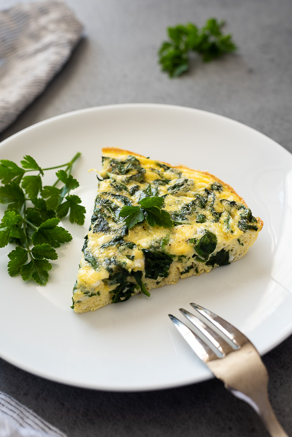 slice of spinach feta frittata on white plate with parsley