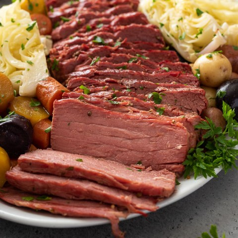 angled front shot of sliced corned beef and cabbage on a white serving platter