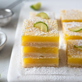 key lime bars stacked up on a white serving board with powdered sugar