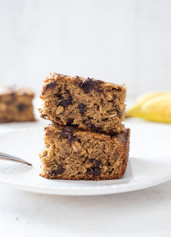 two squares of banana oatmeal cake stacked on a plate