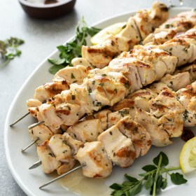 Close up of chicken souvlaki on a white platter with lemon and oregano