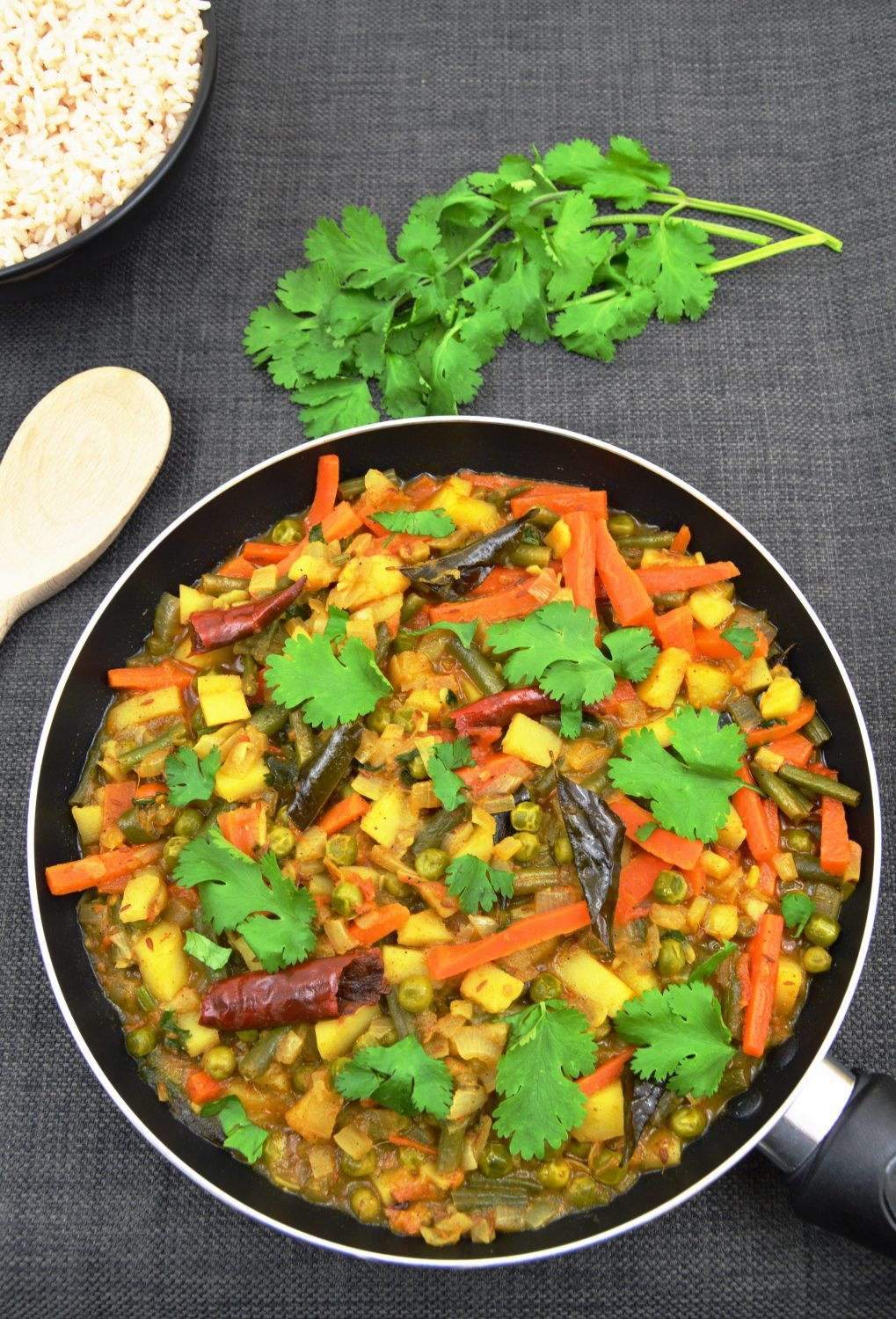 vegetable chettinad in a pan with coriander leaves rice in a bowl