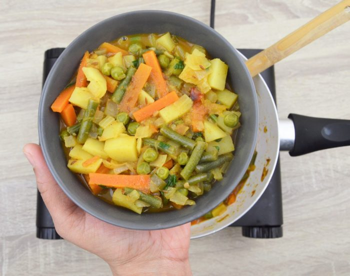 veg curry in a bowl holding in hand