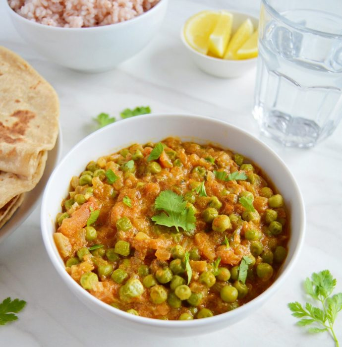 green peas masala in a white bowl with chapatis, brown rice, lemon slices and a glass of water.