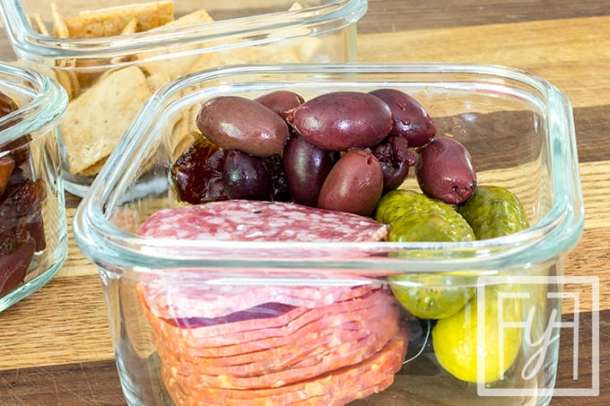 Paleo AIP lunch in glass bowl of olives, salami, pickles