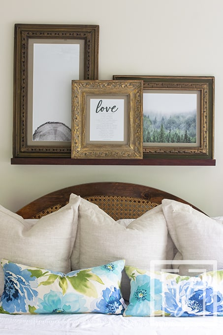 vintage frames on photo ledge over king size bed