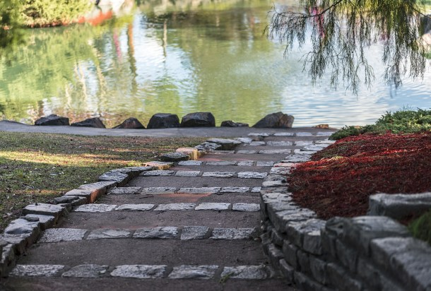 A large outdoor meditation garden with a stone path, plants, and water