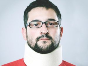Man in red top with neck brace