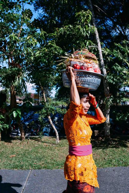 Balinese woman carrying offerings on her head, galungan day 2014