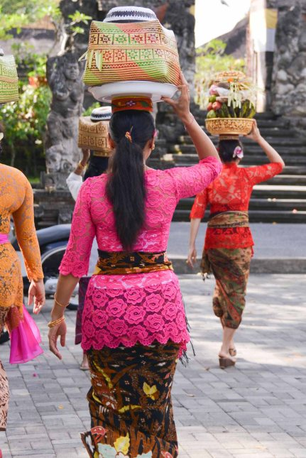 Balinese women in festive clothing carrying gifts and offerings on their head on Galungan day 2014