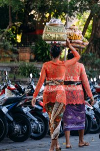 Two Balinese women in festive clothing carrying gifts and offerings on their head on Galungan day 2014