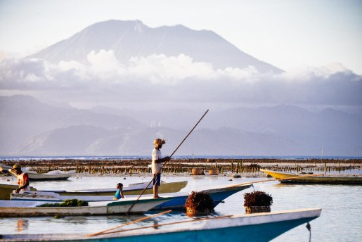 Seaweed farmer on a boat and an afternoon view of Mt. Agung from Nusa Lembongan