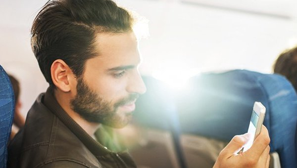 SITA Passenger Survey, man using smartphone on Airplane. Source: SITA, Getty Images.
