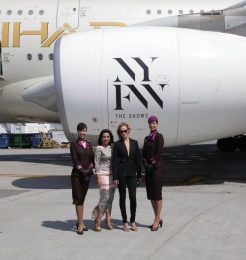 """(From left to right flanked by cabin crew) From runway to runway, Amina Taher, Head of Corporate Communications - Etihad Airways and Supermodel Amber Valletta unveil the airline's A380 livery, featuring an """"NYFW: The Shows""""- branded logo on the aircraft engines and doors at JFK International Airport."""