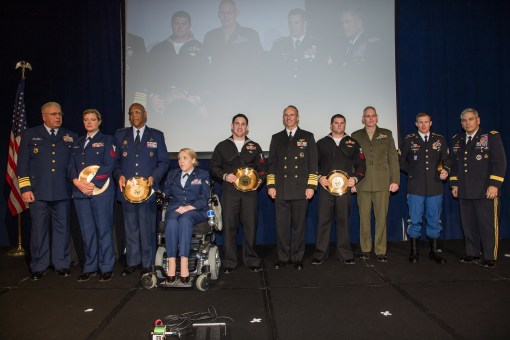 (left to right) HSN1 Janet Combs, SrA Taylor Renfro, HM2 Michael Marchante, HM1 Kevin Toland, and Sgt. Kristopher Ritterhouse hold their awards. Among them stand Air Force Gen. Larry Spencer; Gen. John Campbell, Vice Chief of Staff of the United States Army; Rear Admiral Brian Pecha, Force Surgeon, Marine Force Reserves; Admiral Jonathan Greenert, Chief of Naval Operations; Vice Admiral John Currier, 28th Vice Commandant of the USCG. (photo courtesy Meredith Resnick).