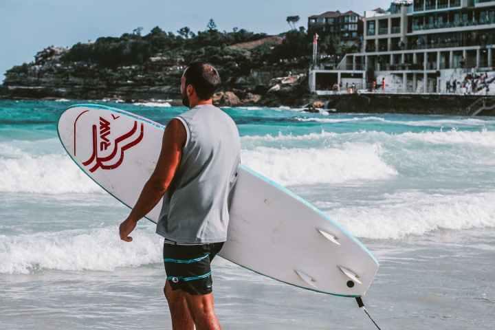 man walking towards body of water holding a surfboard