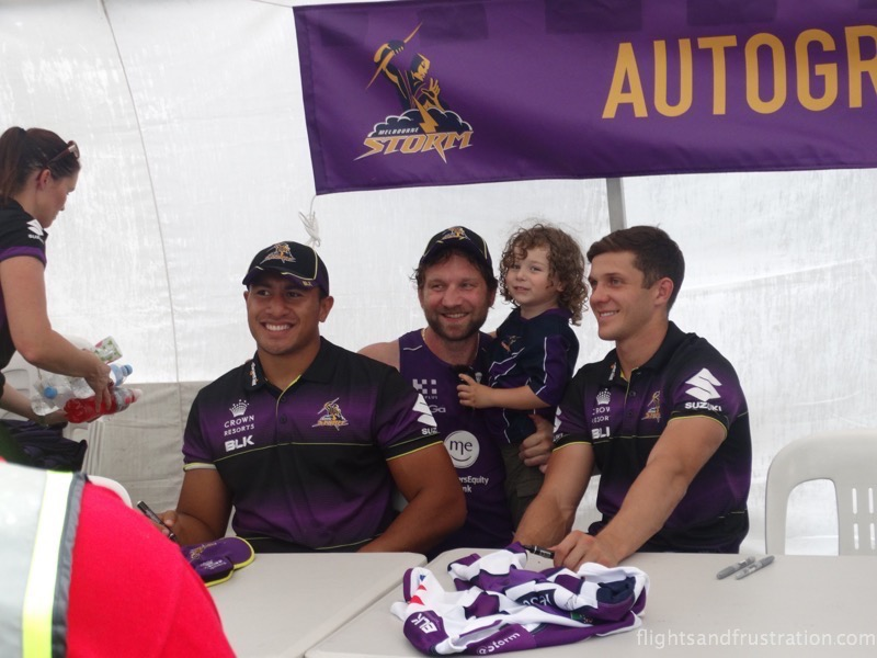 A young fan has a picture with some of the Melbourne Storm players at the melbourne storm family fun day