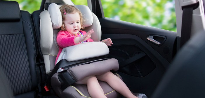 Cute curly laughing and talking toddler girl playing with a toy enjoying a family vacation car ride in a modern safe vehicle sitting in a baby seat with belt having fun.