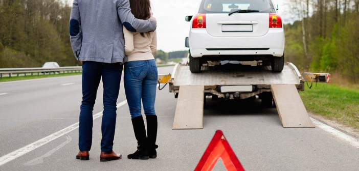 Couple near tow-truck picking up broken car
