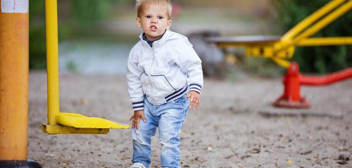 Toddler boy rubbing his leg injured at school on playground