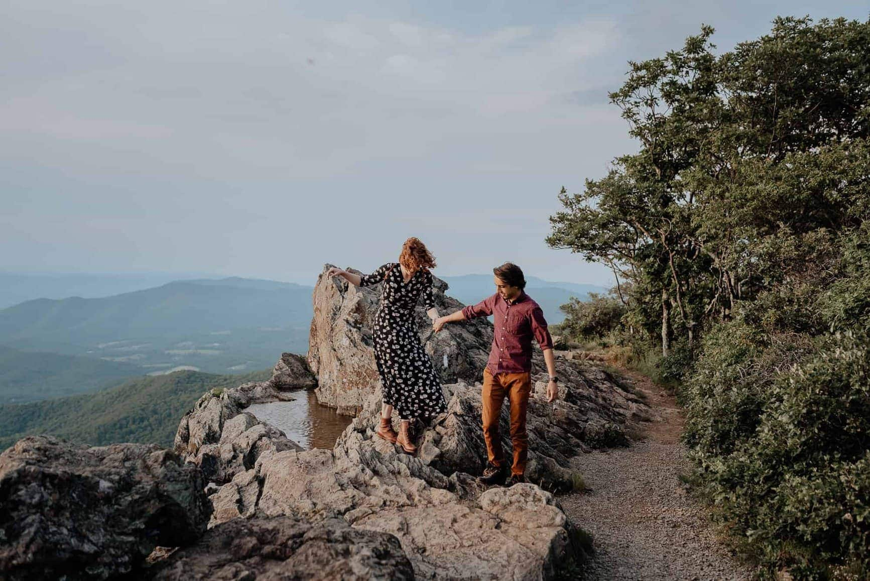 A couple clambers across some large rocks along a cliff in Shenandoah National Park