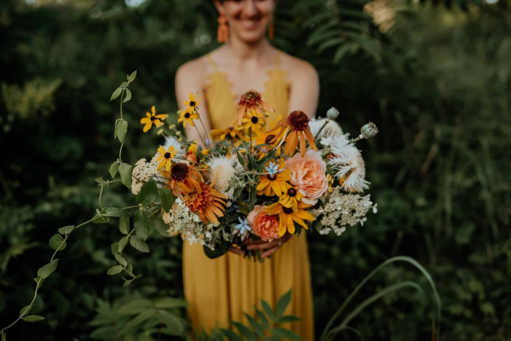 A bride in a yellow wedding dress holds out a lush wedding bouquet.