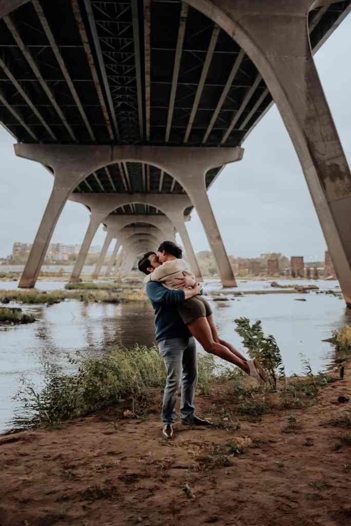 A couple hugs and spins on a sandy beach near the pipeline in Richmond Virginia