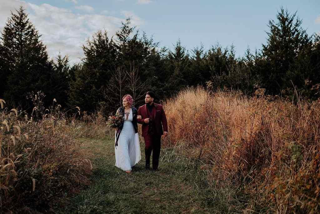A couple walks through a field for their autumn elopement.