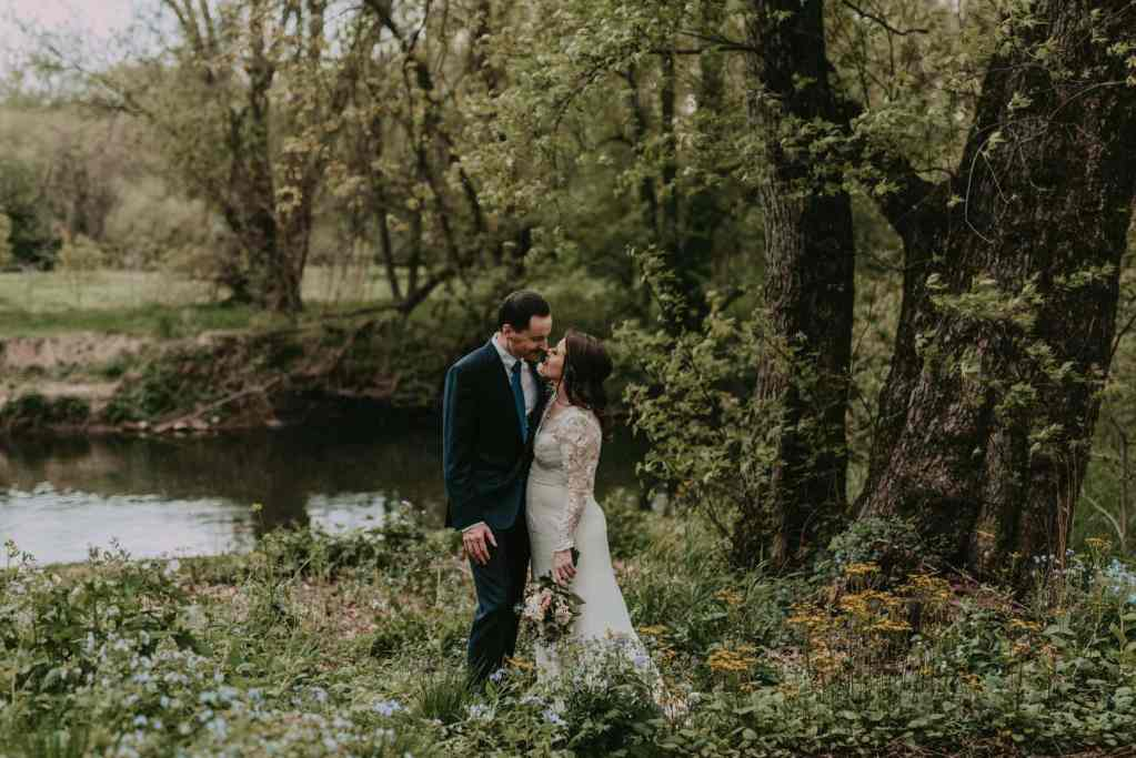 A newlywed couple stands in wildflowers along a riverbank