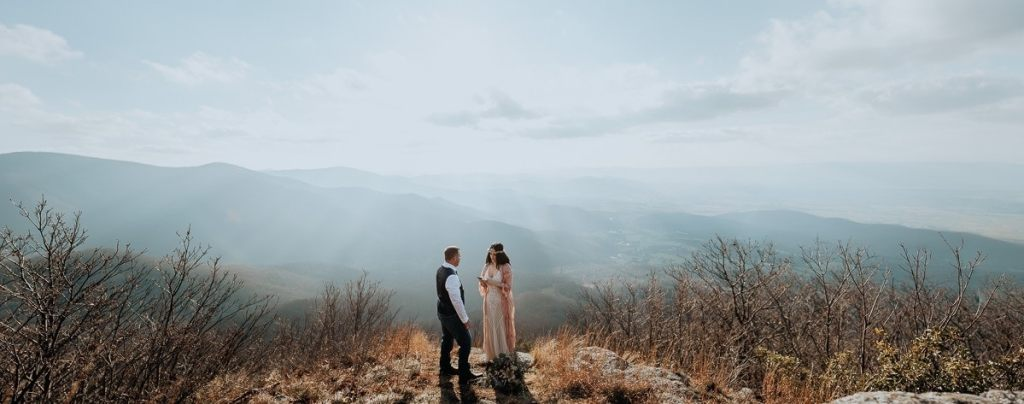 A wide shot of a couple saying their vows on a mountaintop in Virginia