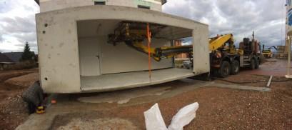 Mit einem Hydraulik-Arm wird die erste Garage gesetzt
