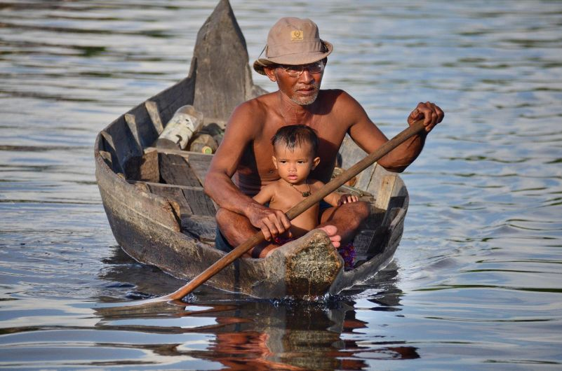 Man Canoes with Son in Floating Village