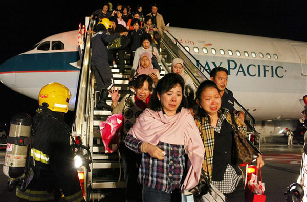 Passengers on Cathay Pacific flight CX715 disembark from the aeroplane after it landed safely at Changi Airport in Singapore