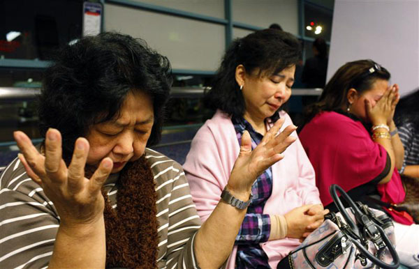 Passengers of Cathay Pacific flight CX715, an Airbus A330 passenger jet, pray after they were evacuated after an emergency landing at Singapore Changi Airport