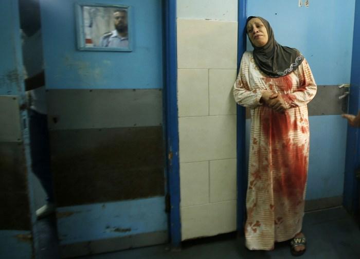 一位巴勒斯坦女士在醫院內哭泣。身上的血,來自在炮火中受傷的家人。