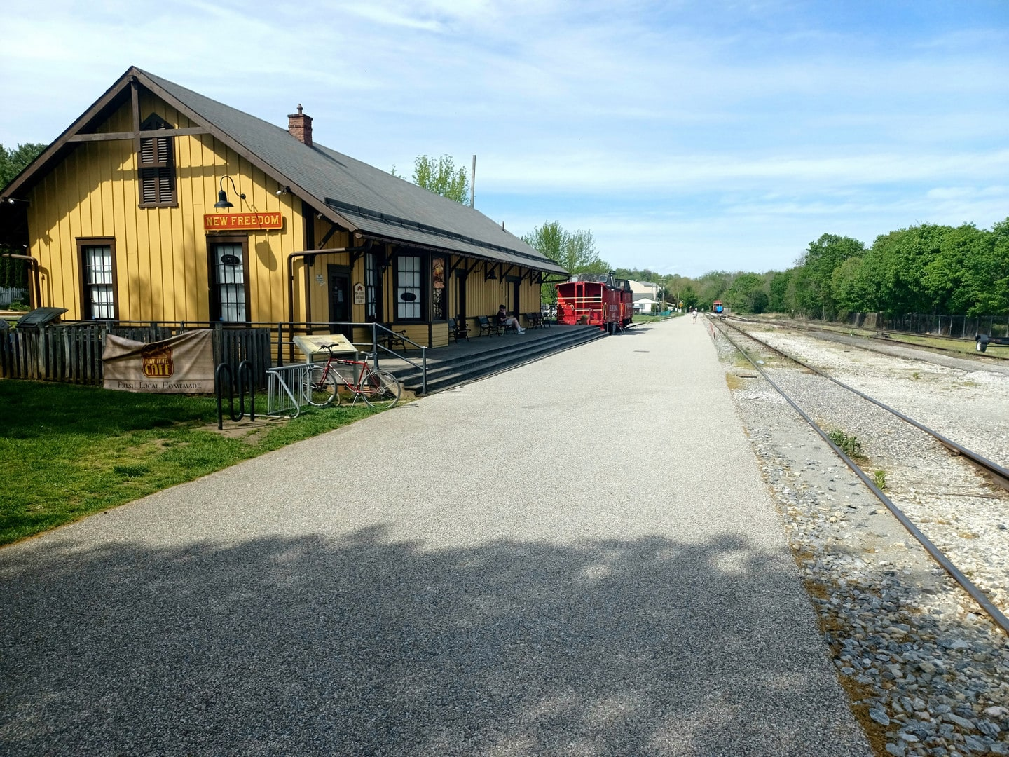 A wide gravel trail runs between the railroad and an old yellow railroad building
