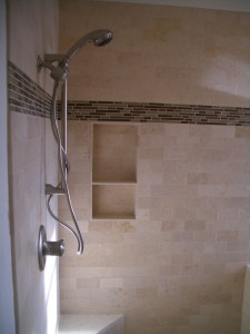 Travertine niche in subway style shower with glass liner above
