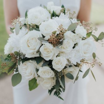 Mostly white roses with other white seasonal flowers plus seeded eucalyptus