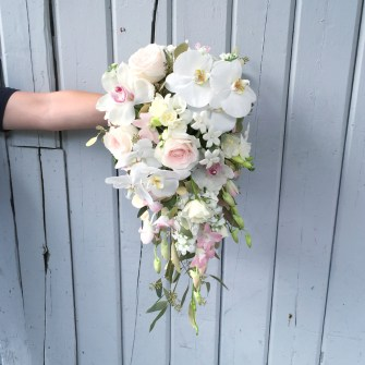 Cascading multiple types of orchids and roses bouquet