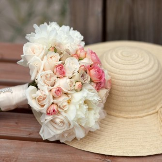 pink white casual beach bridal bouquet next to a floppy beach hat