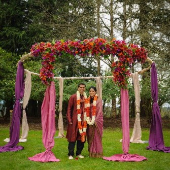 round mandap with Indian couple wearing garlands