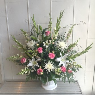 Large white with a touch of pink flowers in plastic urn