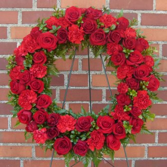 Red wreath standing spray of carnations and roses