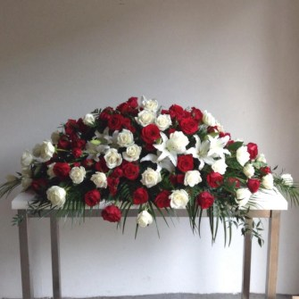 Casket spray of red & white roses with a touch of white lilies