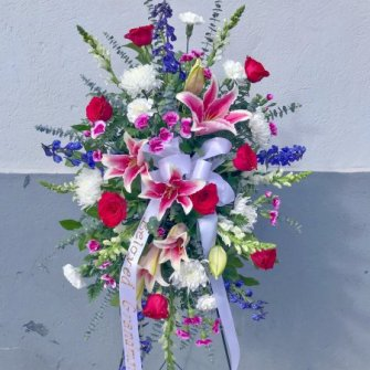 Medium standing spray of stargazer lilies, red roses, blue delphinium