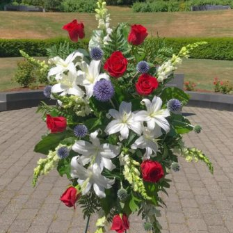 Medium standing spray of white lilies, red roses and blue globe thistles