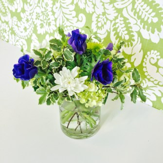 mini arrangement of blue anemones, green hydrangeas and white flowers