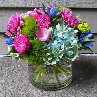 medium low cylinder arrangement of color spring flowers