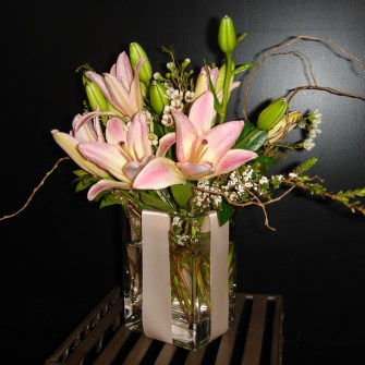 pink lilies in a small present vase