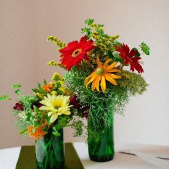 mixed flowers in cut wine bottle